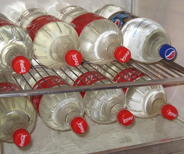 Вода в пластиковых бутылках в холодильнике