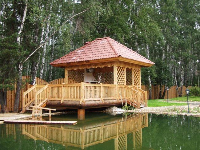 Деревянная беседка с террасой у пруда